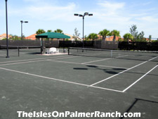 View of the clay tennis courts adjacent to the clubhouse. Engage in a rousing tennis match after work, then relax by the pool afterward.